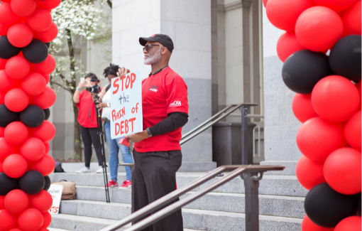 """A CFA member holds a sign that reads """"stop the rain of debt"""" at a rally with red and black balloons."""