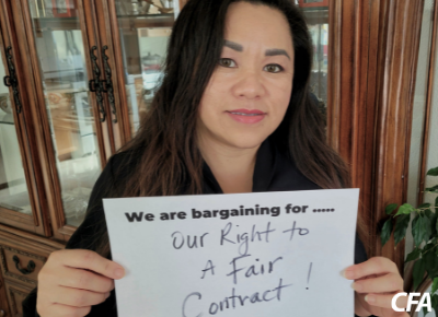 """Vang Vang holds a sign saying """"we are bargaining for our right to a fair contract!"""""""