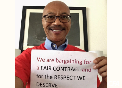 """Charles Toombs holds a sign reading """"We are bargaining for a fair contract and for the respect we deserve."""""""