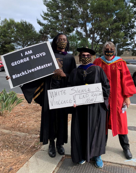 CFA members join others protesting the police shooting of George Floyd wearing their caps and gowns and holdingsigns.