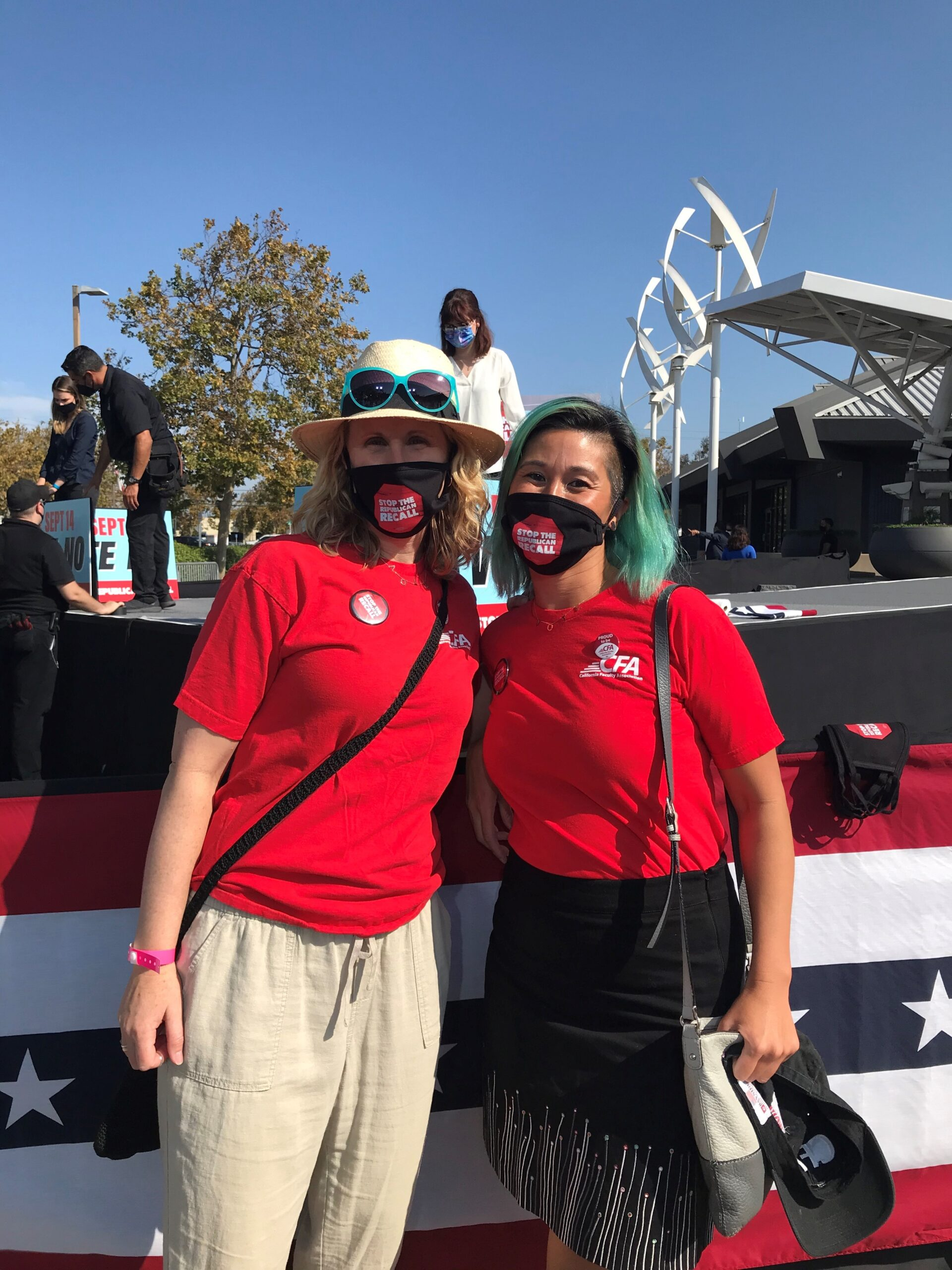 CFA East Bay members Amy Below and Danvy Le attend attend a No on the Recall rally in their red CFA shirts and anti-recall black and red face masks.